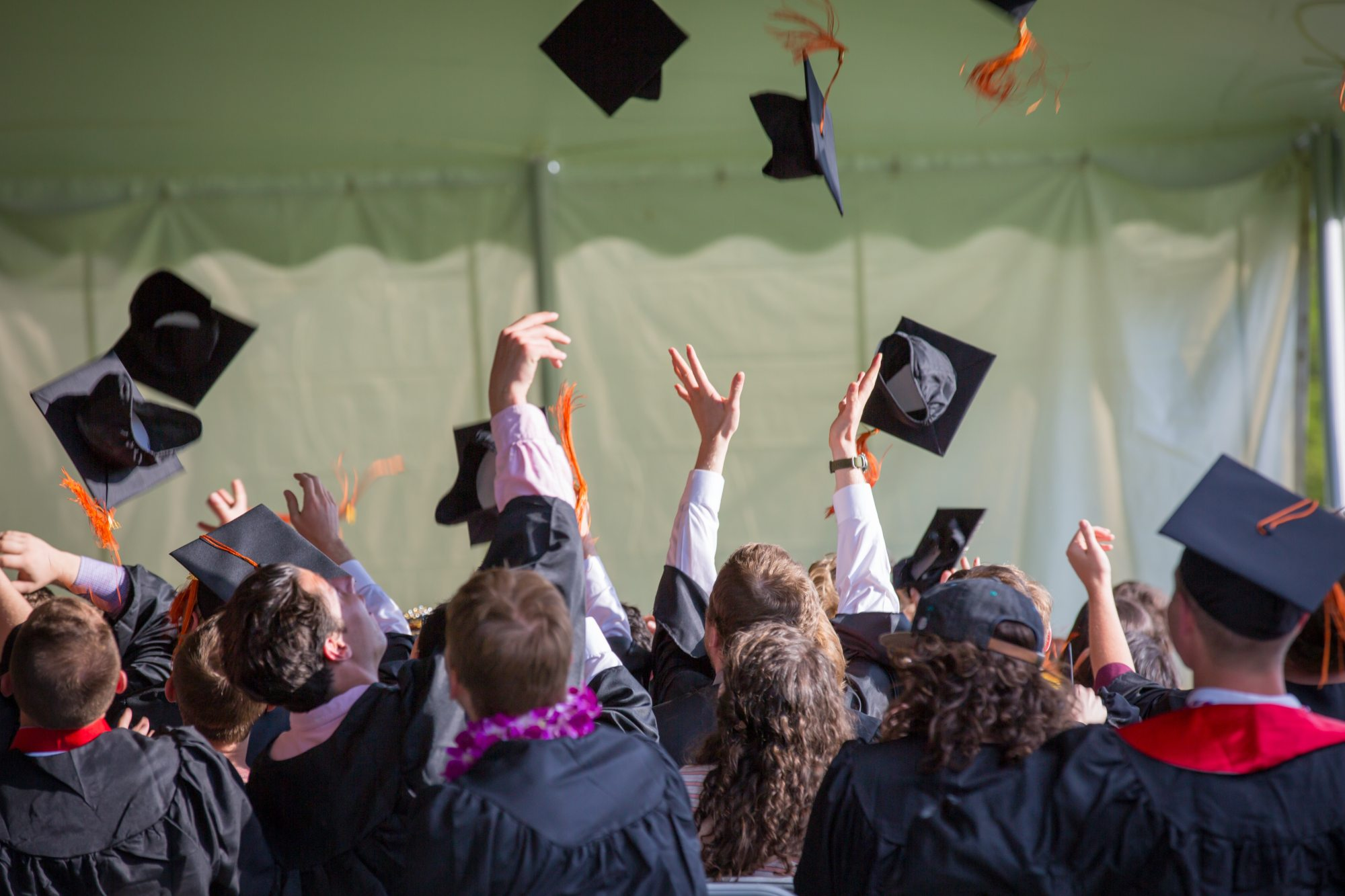 Graduates tossing their hats up at graduation