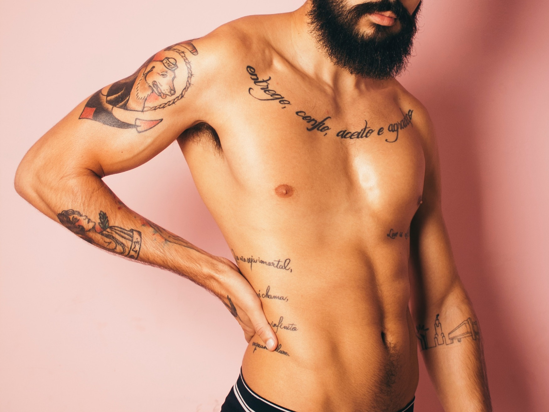 A bearded, tattooed man, with one hand on his waist