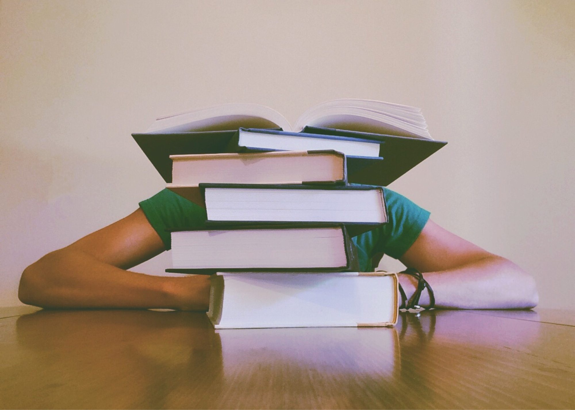 Student behind a stack of books
