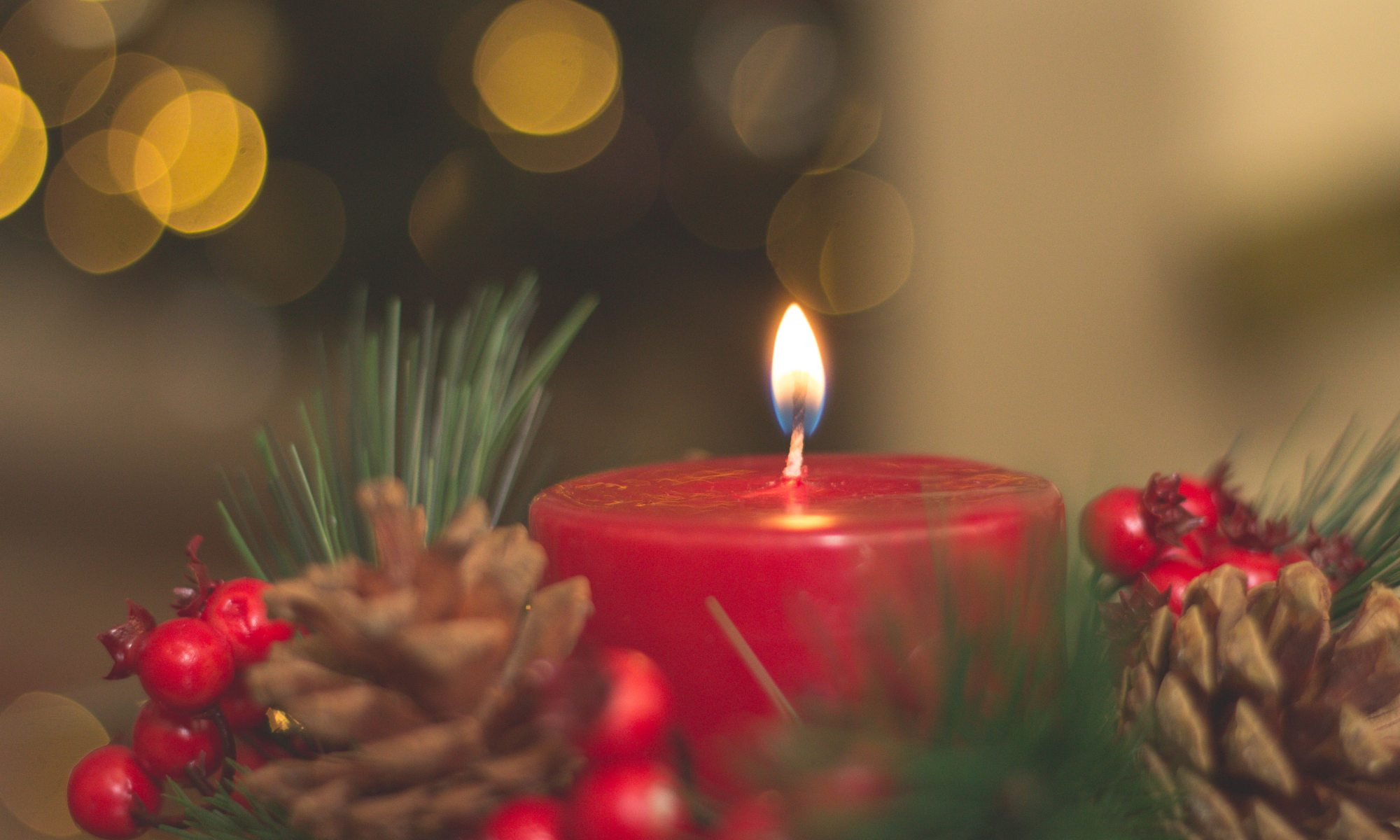Red candle with holiday decorations
