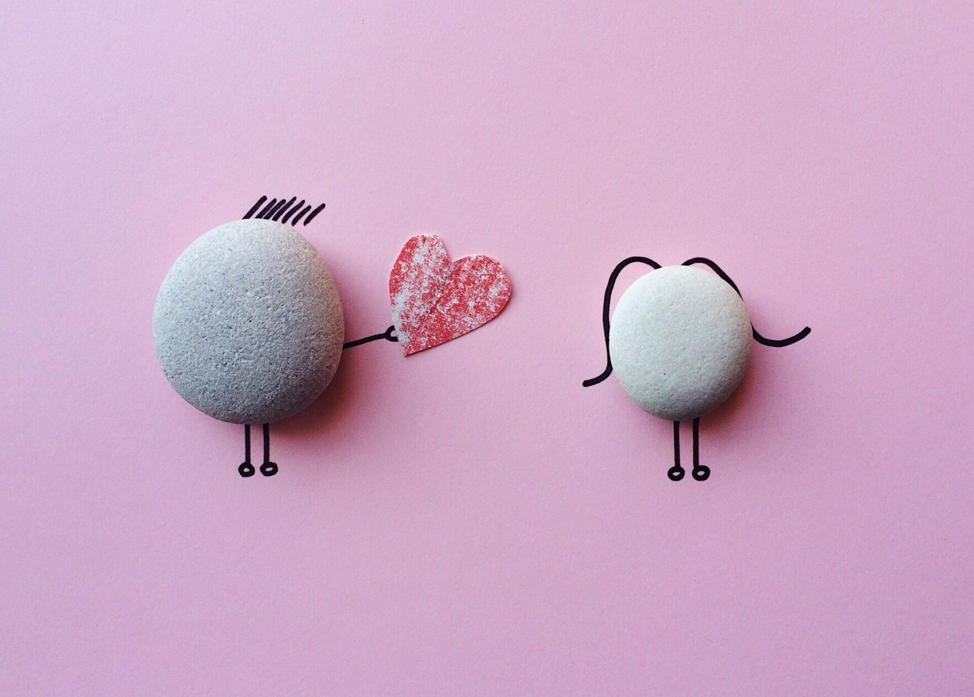 Stick figures made of rocks, one giving a heart to the other