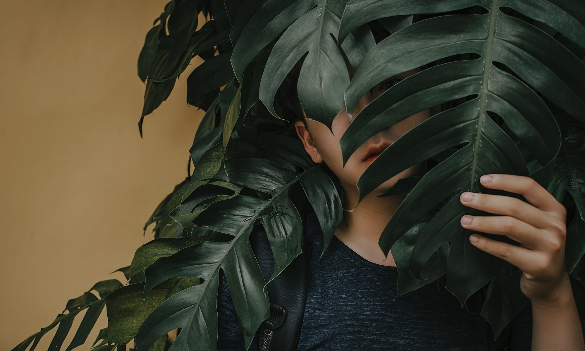 Young person behind leaves