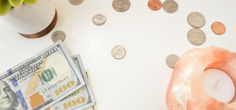 Stack of bills and scattered coins on a desk