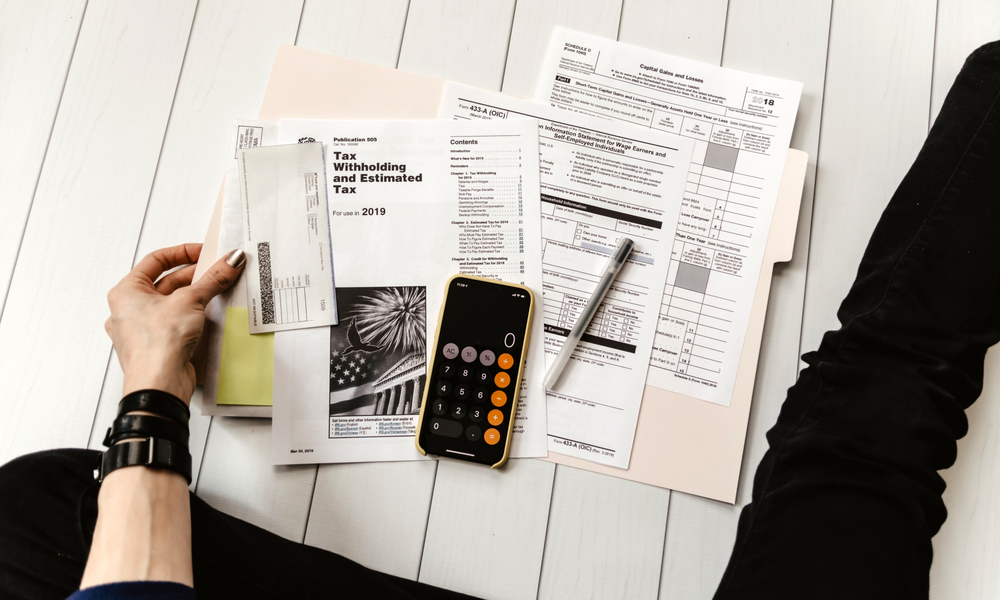 Person with tax forms and phone calculator