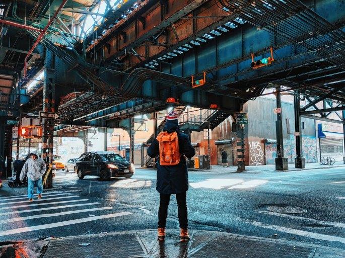 Person on a street corner underneath aboveground subway tracks