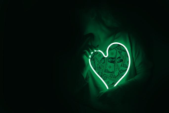 A green neon heart with dollar bills inside